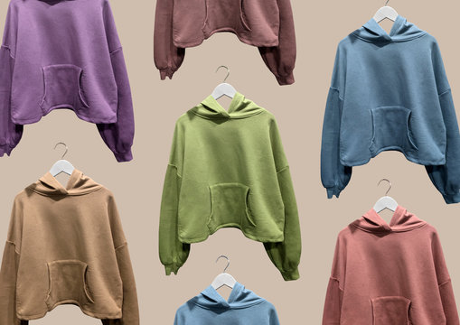 Multi colored basic hooded sweatshirts on hangers isolated on brown background.  Composition of clothes. Flat lay. Minimal style. Composition of clothes. Pattern. Trendy clothes collage. Hoodie