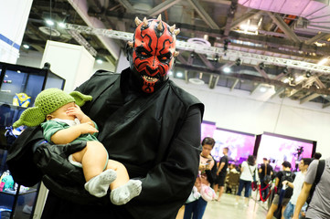 A cosplayer dressed as Darth Maul from Star Wars, carrying a child dressed in a Yoda hat, poses during the Singapore Comic Con, in Singapore