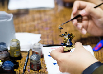 An attendee paints a tabletop gaming figurine during the Singapore Comic Con, in Singapore