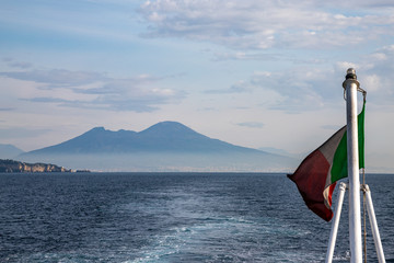 Vesuvio, Naples, Campania, Italy: the Gulf of Naples and Vesuvius volcano in the background seen from the sea with Italian flag in foreground.