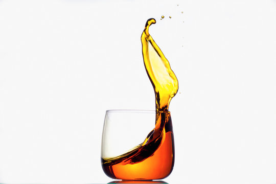 Splash of yellow liquid in a transparent glass
