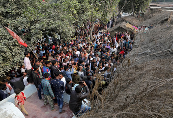 People gather outside the house of a 23-year-old rape victim, who died in a New Delhi hospital on Friday after she was set on fire by a gang of men, which included her alleged rapists, in Unnao