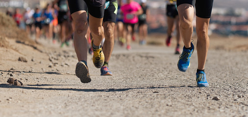 Runners running shoes on trail run. Ultra running athletes legs close up on running in rock path trail