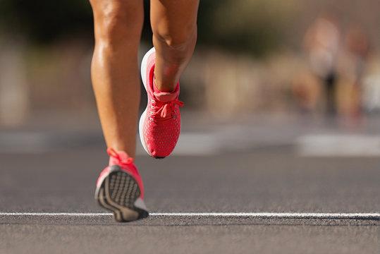 Athlete runner feet running on road close up on shoe , marathon running race