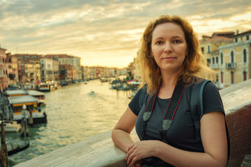 Portrait of young woman on Rialto Bridge at sunset, Venice, Italy. Tourist poses on background of Grand Canal.