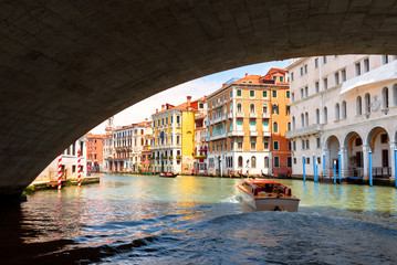 Fototapete - Grand Canal in summer, Venice, Italy. Motor boat sails under famous Rialto Bridge, landmark of Venice.