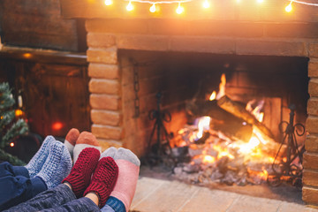 Legs view of happy family lying down wearing warm wool socks with fire place and vintage lights in...