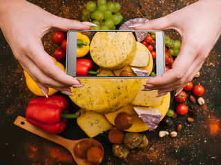 Food blog. Home cooking. Woman taking picture of cheese and vegetables on smartphone camera.