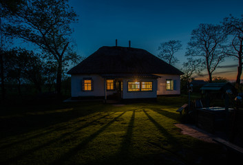 Fototapeta Landscape with a cosy country house at night. Window light. Silhouette of trees. Ukrainian night. obraz