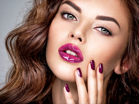 Beautiful and stunning woman with  purple lipstick on lips and fingernails.