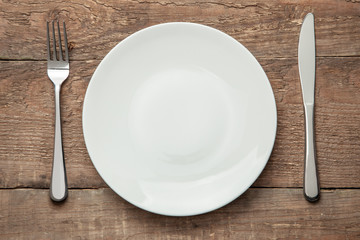 Empty white plate with knife and fork on a wooden table