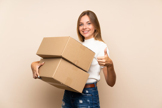Young blonde woman over isolated background holding a box to move it to another site with thumb up