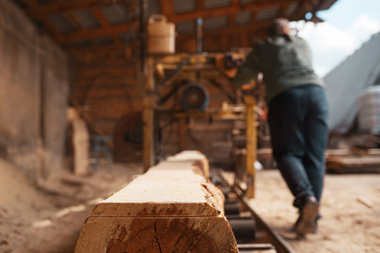 Joiner works on woodworking machine, lumbering