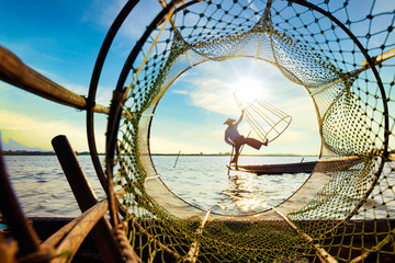 Myanmar travel attraction landmark - Traditional Burmese fisherman at Inle lake, Myanmar famous for their distinctive one legged rowing style