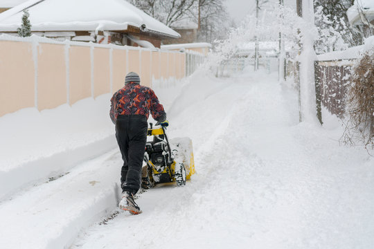 man operating snow blower to remove snow on driveway. Man using a snowblower. A man cleans snow from sidewalks with snowblower