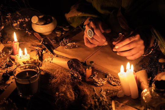 Hands fortune teller over an ancient table with herbs and books. Manifestation of occultism in the form of divination