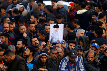Supporters of Iraqi Shi'ite cleric Moqtada al-Sadr carry his picture near his home, after it was attacked, in the holy city of Najaf