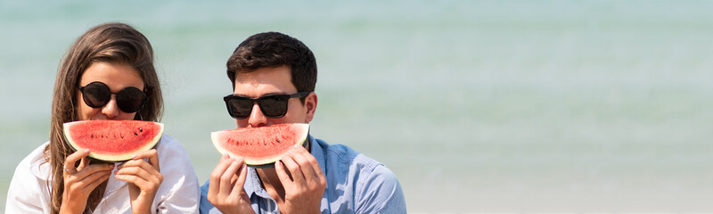 Young Couple wear sunglasses holding slice of watermelons.