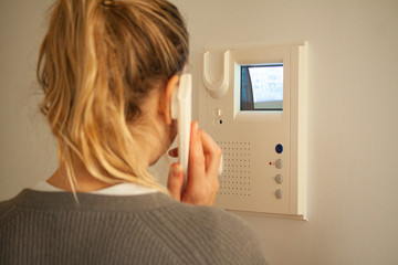 Blonde woman answering a call at a door phone while looking at the screen on the CRT display. Video intercom equipment. Selective focus image. Wall mural