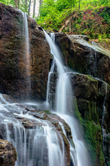 waterfall skakalo in the forests of transcarpathia. rapid water stream runs down the huge boulders. clear water of carpathian nature in springtime. long exposure
