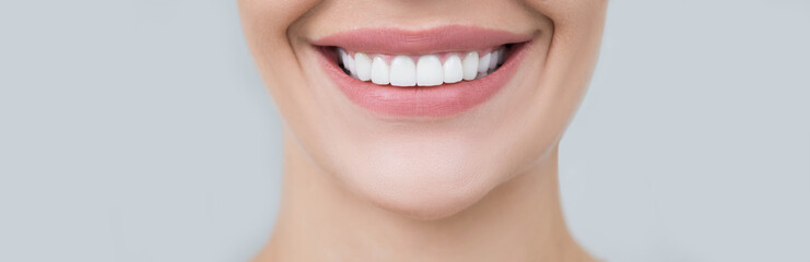 Perfect female smile on gray background. Healthy white teeth, advertising dentistry
