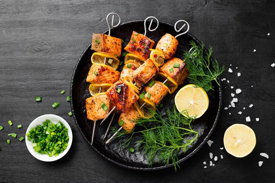Baked salmon skewers with lemon and green onion.