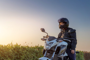 Asian woman with helmet and wearing and fasten before riding big bike motorcycle on the road for safety Wall mural