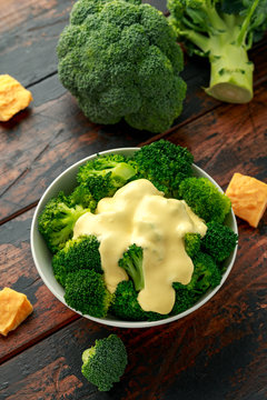 Broccoli with cheese sauce in white bowl on wooden table