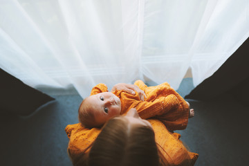 Mother and baby daughter looking at window family lifestyle mom and infant child at home maternity...