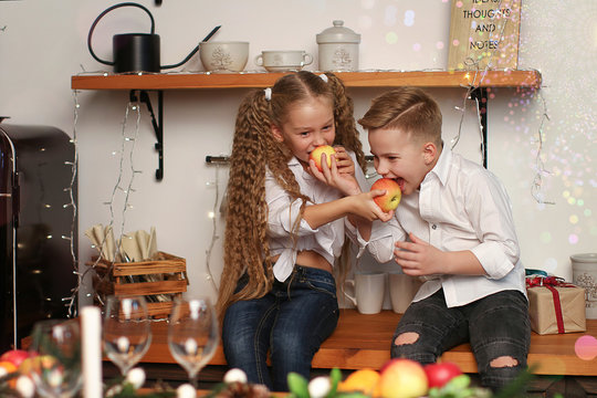Boy and girl celebrate New Year, drink juice, eat fruit and make wishes in the New Year decorations