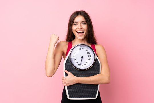 Pretty young girl with weighing machine over isolated pink background with weighing machine and doing victory gesture
