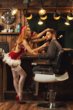 Side view of shaving process in barbershop. Sexy female stylist in short red dress shaving handsome bearded male client in smart suit sitting in barbershop. Concept of servicing.