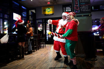 """Men in Santa Claus and elf outfits pose for a photograph in The Field House after the """"Running of the Santas"""" annual pub crawl never materialized in Philadelphia"""