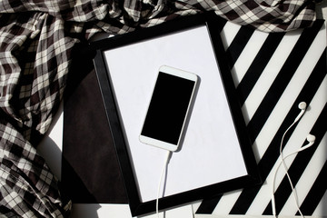 A white smartphone and headphones on a black white background with a strip. Top view, shadows