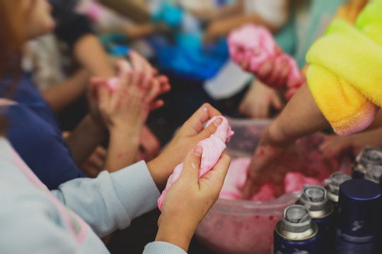 Group of kids making a multicoloured slime, pink, blue and white slime toy on kids birthday party, kid playing with slime, homemade slime