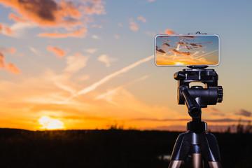 Smartphone on tripod capturing image of stunning sundown Fotomurales