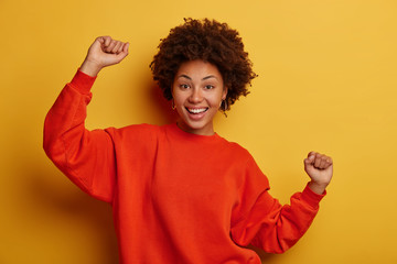 Image of joyful smiling Afro American woman has fun, expresses happines, clenches fists, enjoys party with friends, makes celebratory dance move, dressed in red jumper, celebrates awesome day Fotobehang