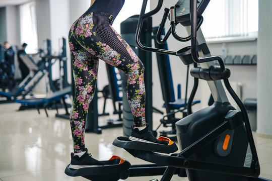 Woman doing legs exercise on stair steppers machine, in gym. selective cropped photo, fit woman. Closeup.
