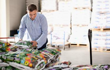 Man choosing compost soil in plastic bags in hypermarket