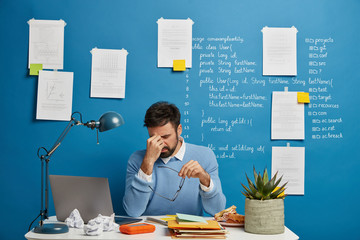 Exhausted businessman rubs nose, takes off spectacles, suffers from eye strain and headache, has problems at work, sits in coworking space with laptop computer, blue wall with written notes.