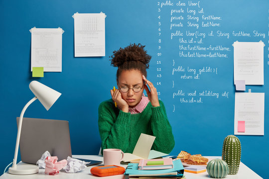 Stressful student feels unwell, has dizziness and headache, unable to work, writes down list to do in notepad, poses against blue background with written information. Employee feels strong migraine