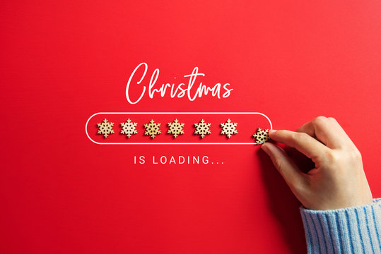 Woman hand putting snowflakes christmas loading bar on the red background.