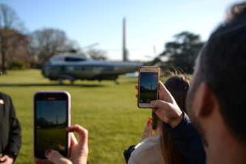Visitors take photos as U.S. President Donald Trump departs the White House en route to Florida, in Washington