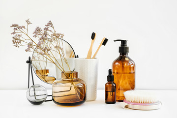 Branch in a glass vase, mirror, bamboo toothbrush and cosmetics products on white table. Decor for interior. Stylish decoration for home.