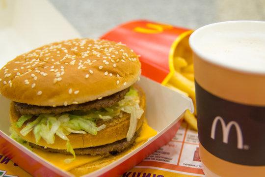 Hamburger menu in McDonald's restaurant. Fries, coffee capuccino, Big Mac. Fastfood and junk food concept Russia, Saint-Petersburg, December 24, 2018