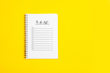 Piece of paper with to do list on it, on a yellow background