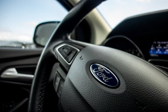 A steering wheel of a modern Ford Focus car prepared to travel around the country with bokeh effect