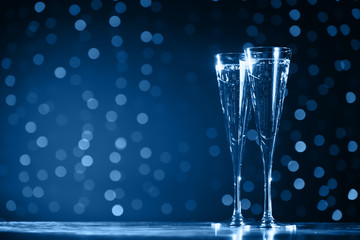 Wall Mural - Two glasses of champagne on classic blue bokeh background. Holiday concept. Festive bokeh background. Horizontal, toned