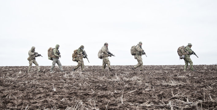 Army soldiers group on march in muddy field