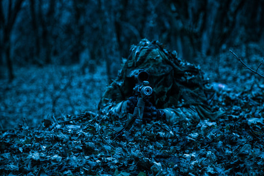 Army military sniper hiding on ground in forest leaves
